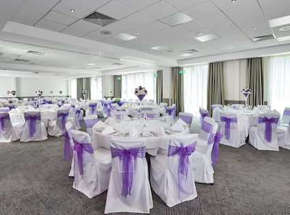 Meeting Room Set Up for Wedding Reception With Large Windows, White Chairs With Purple Bows, and Round Tables With Place Settings and Flowers on White Linens