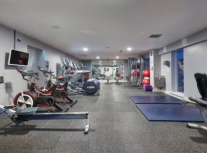 Fitness Center With TV, Cardio Equipment, Mirrored Wall, Wall Clock, Water Fountain, and Exercise Mats