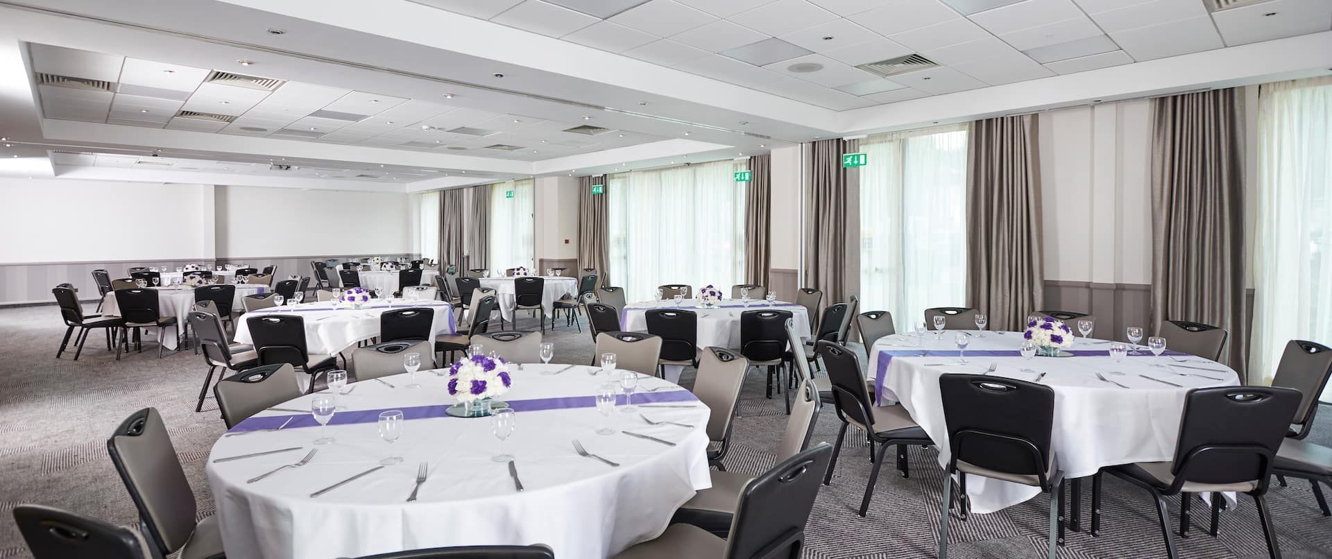 Meeting Room Set Up for Social Event With Large Windows, Grey Chairs, Round Tables With Place Settings and Flowers on White Linens