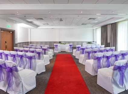 White Chairs With Purple Bows Arranged Theater Style, Red Carpet Down the Center Aisle Leading to Two Chairs in Front of Table With White Flowers, and Large Window in Meeting Room Set Up for Wedding Ceremony