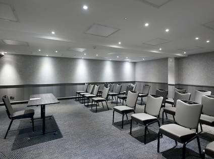 Meeting Room Arranged Theater Style With Rows of Chairs Facing Presenter's Table