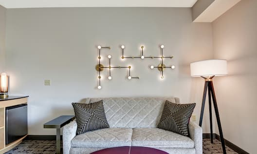 Guestroom seating area with couch and decorative lamps
