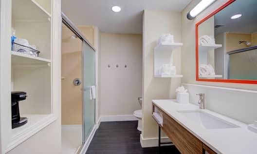 Guest bathroom with walk-in shower, toilet, vanity mirror, sink, and towels