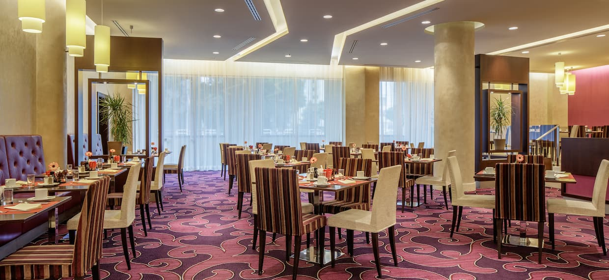 Windows With Sheer Drapes, Booth, Tables With Place Settings, and Chairs in Dining Area of OPUS Restaurant