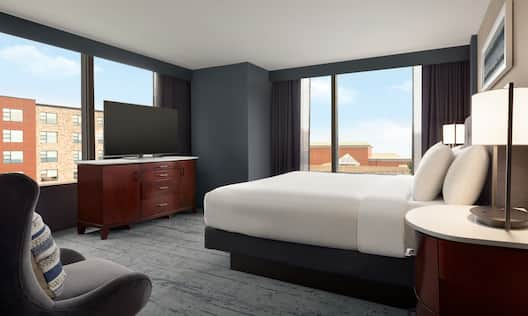 Guest Room with Large Bed Soft Chair HDTV and City View