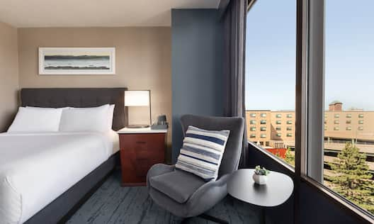 Guest Room with Bed Soft Chair and City View