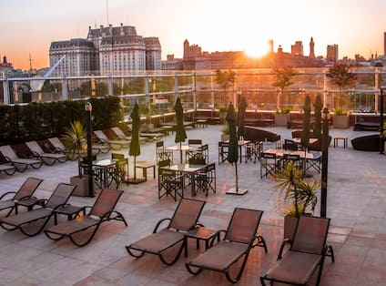 Rooftop Terrace with Tables and Chairs at Sunset