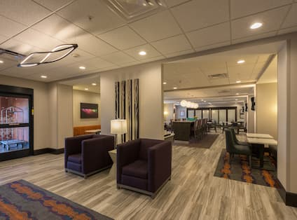 View of Lobby Lounge Area  with Two Square Chairs, and Tables with Additional Seating in the Background