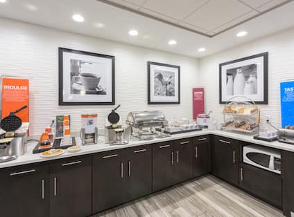 Breakfast Bar Area with Waffle Irons, Pastries, Cereal, and Condiments