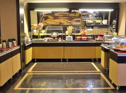 Hot and Cold Buffet and Beverage Selections in Breakfast Area With Plates, Utensils, and Condiments