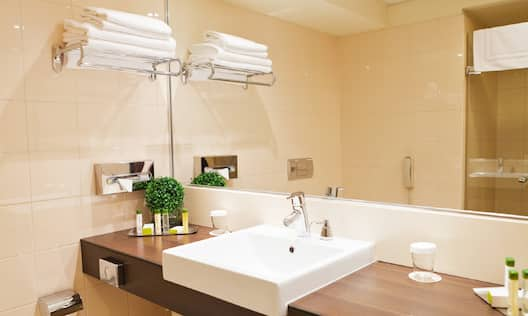 Fresh Towels, Shower With Glass Doors Reflected in Large Vanity Mirror, Sink, and Toiletries in Queen Room