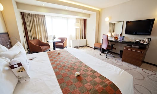 King Bed, Two Armchairs and Table by Large Window With Open Drapes, Work Desk, TV, and Hospitality Center in Superior Room