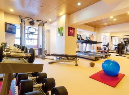 Fitness Center With Free Weights, TV, Weight Machine, Bench, Cardio Equipment, Blue Exercise Ball, and Mirrored Wall