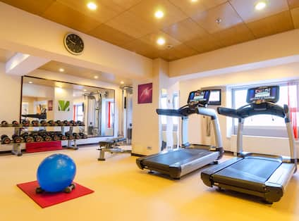 Fitness Center With Wall Clock, Large Mirror, Free Weights, Bench, Treadmills Facing Windows, and Blue Exercise Ball