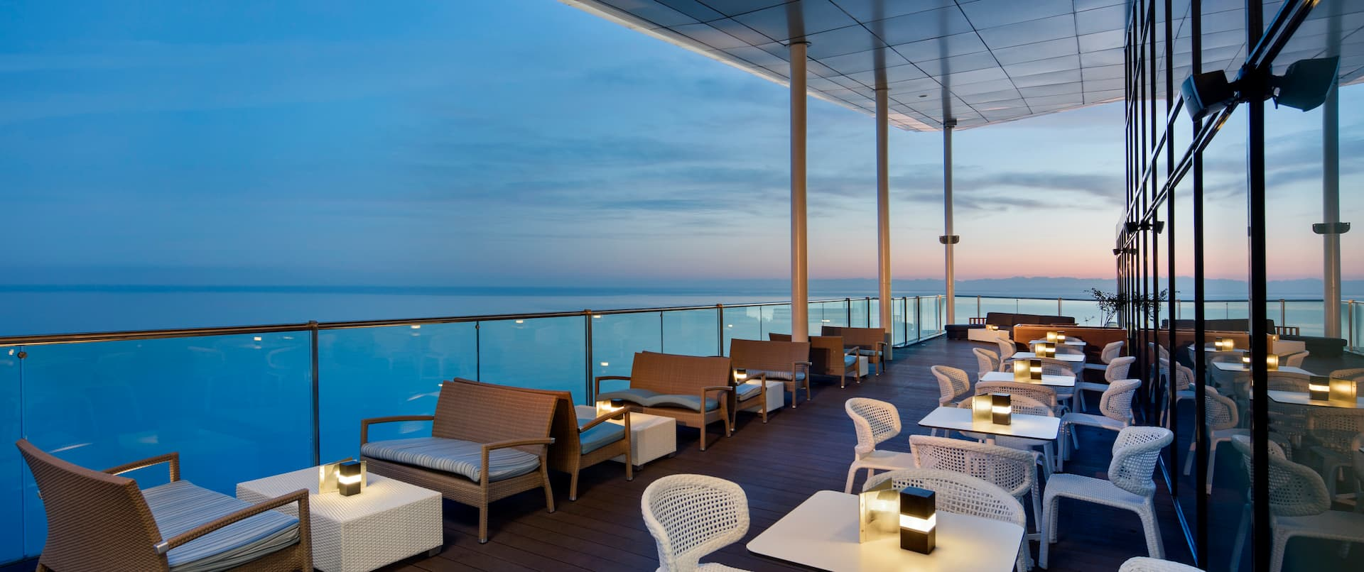 Outdoor Balcony Dining Area at Night with Ocean View