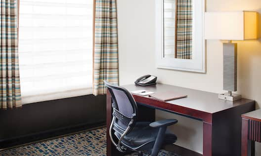 Detailed View of Window With Open Drapes, Mirror Above Work Desk With Phone and Illuminated Lamp,, and Ergonomic Chair