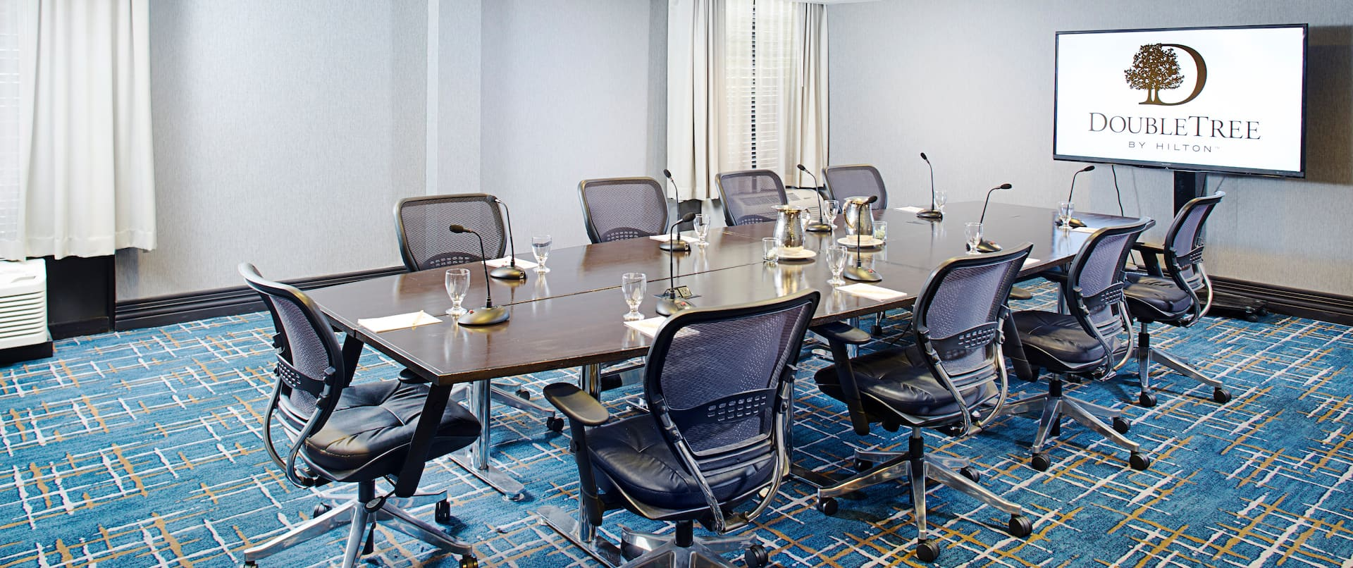 Wall Art, Seating for Nine at Table With Microphones, Water Pitchers, and Glasses Facing TV in Executive Ballroom