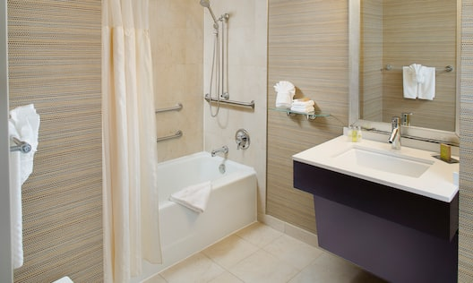 Fresh Towels, Shower Seat, Accessible Bathtub With Grab Bars and Handheld Showerhead, Vanity Mirror, Sink, Towels, and Toiletries