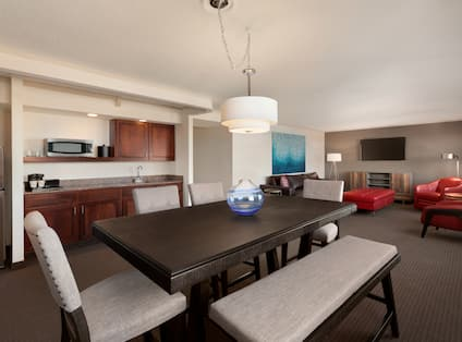 Guest Suite Lounge Area with Beverage Station, Dining Table, Armchair and Wall Mounted HDTV