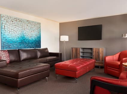 Guest Suite Lounge Area with Sofa, Footrest, Armchairs and Wall Mounted HDTV