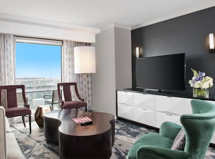 Guest Suite Lounge Area with Sofa, Coffee Table, Three Armchairs, HDTV and Outside Balcony
