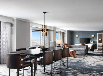 Guest Suite Lounge Area with Dining Table, Chairs, Sofa and HDTV