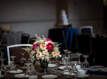 Small floral centerpiece with wine glasses.