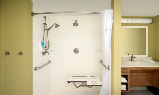 Roll In Shower With Grab Bars, Seat, and Handheld Showerhead, Vanity Mirror, Sink, Fresh Towels, and Toiletries in Accessible Bathroom