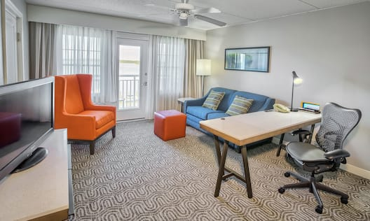 Queen junior suite with TV, sitting chair, sofa, desk, chair and door to patio.