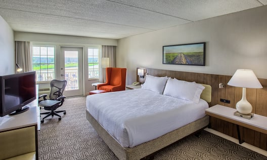 King Bed Between Two Illuminated Lamps and Bedside Tables, TV, Work Desk, Balcony Door With Open Drapes, Illuminated Floor Lamp, and Armchair in Guest Room