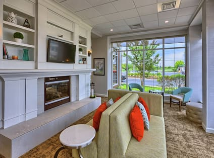 Soft Seating Around Fireplace in Lobby Lounge Area With Large Window