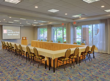 Meeting Room With U-Shaped Table, Chairs, Presentation Screen, and Podium
