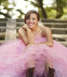 Happy Teen Girl Sitting on Stairs Wearing Pink Quinceañera Dress