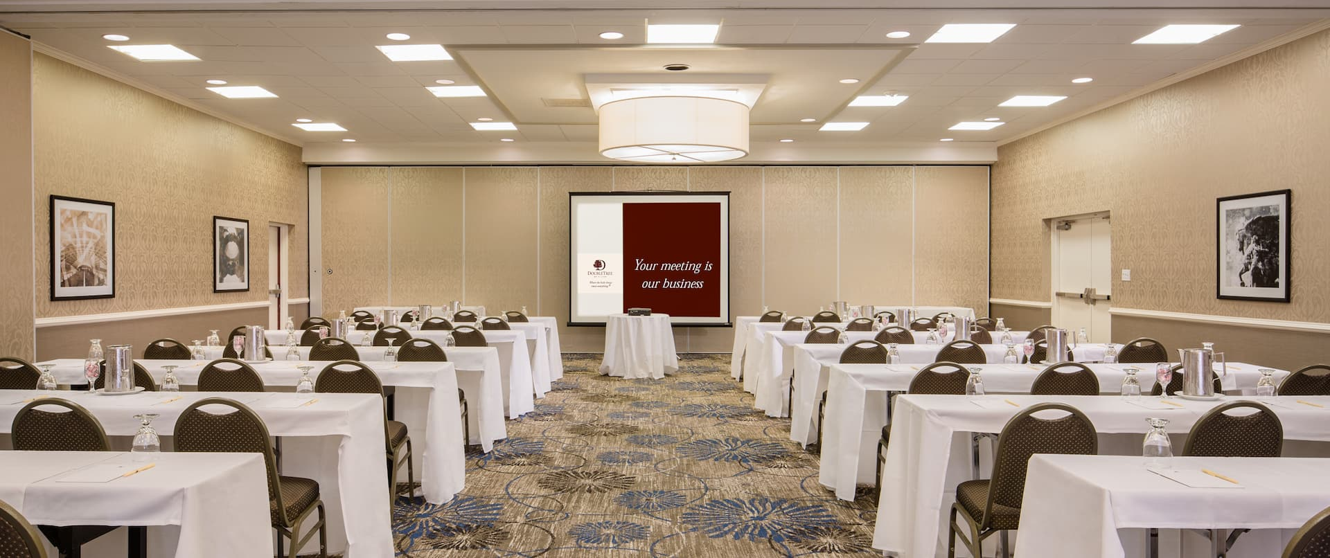 Classroom Setup in Ballroom With Wall Art, Tables and Chairs Facing Projector Table and Presentation Screen