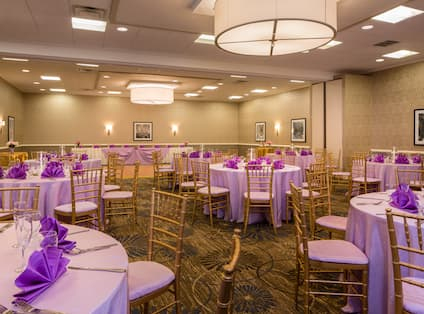 Round Tables With Place Settings, Purple Napkins, and Candles on White Linens, Dance Floor, and Head Table in Event Space