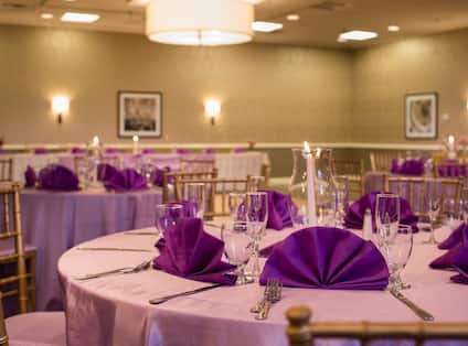 Place Settings, Purple Napkins, and Candles on Round Tables With White Linens Set Up for a Wedding