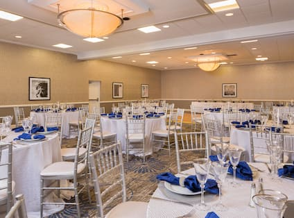 Banquet Setup in Meeting Room With Place Settings and Blue Napkins on Round Tables With White Linens Set Up for a Wedding