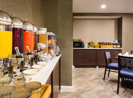 Beverages, Glasses, Plates, Utensils, and Food Selections on Counter in Breakfast Area With Dining Table