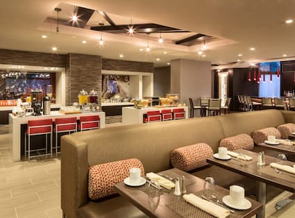 Tables, Booth Seating, and Food Service Area  in XC Bistro With Counter Seating at the Bar
