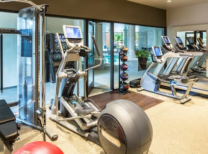 Fitness Center With Red Exercise Ball, Weight Machine, Bench, Cardio Equipment, Glass Entry Door, Weight Balls, and Large Mirror