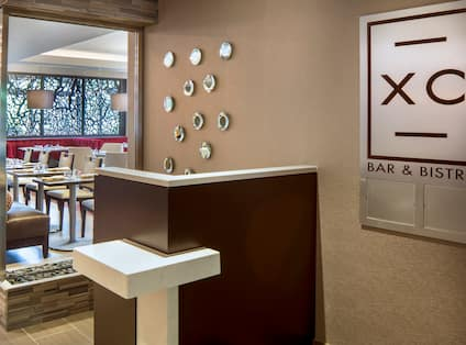 XC Bar & Bistro Signage on Wall by Hostess Area at Entrance of Restaurant and View Into Dining Area