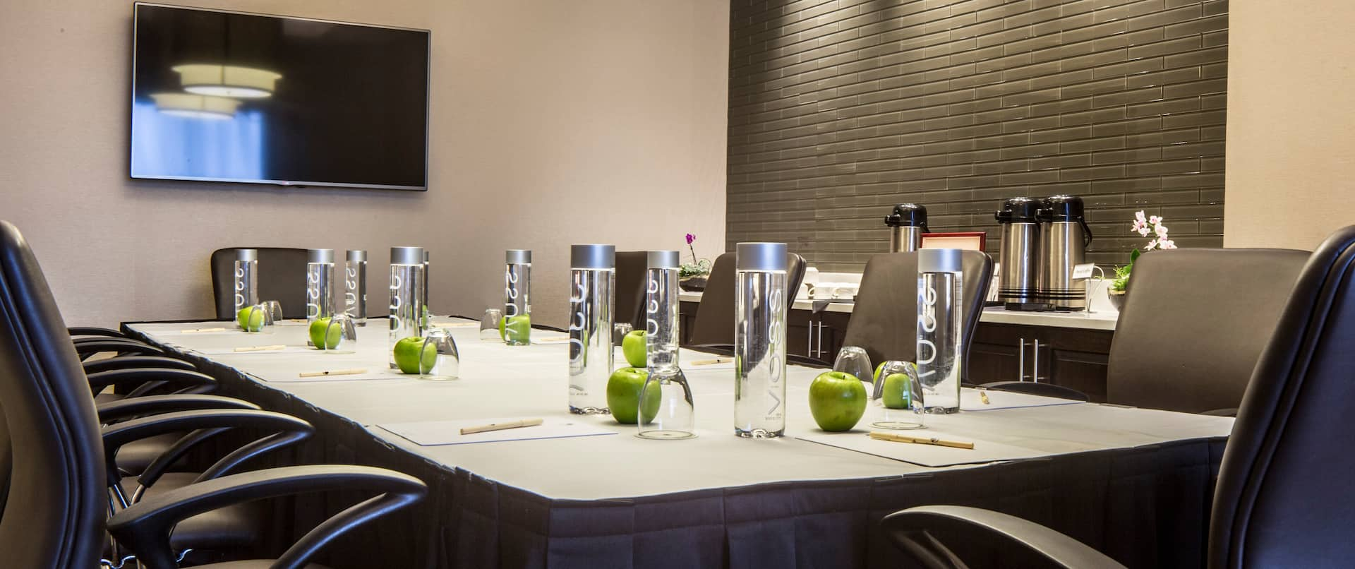 TV, Refreshment Center, Black Chairs, Water Bottles and Green Apples on Table in a Boardroom