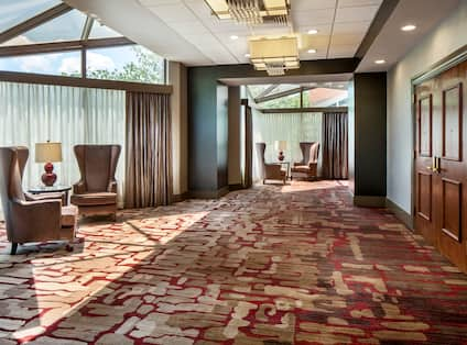 Windows With Sheer Drapes, Armchairs, Illuminated Lamps on Tables, Wooden Entry Doors, and Cocktail Tables in Corridor Outside of Meeting Space