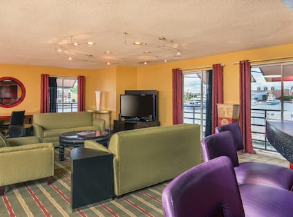 Executive Lounge Area with Green Sofas, HDTV, Purple Bar Stools and Bar Counter