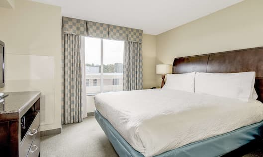 King bed with large window and TV
