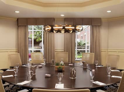 Elegant boardroom in neutral colors set up for a meeting with table in circular setup