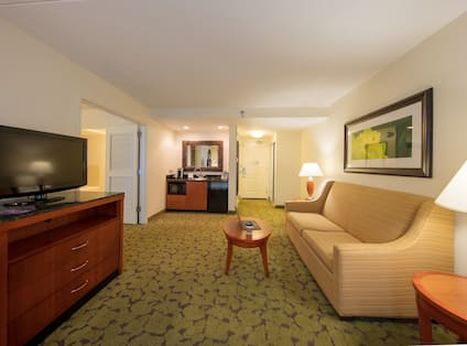 Guest Suite Lounge Area with Sofa, Coffee Table, HDTV and Beverage Station