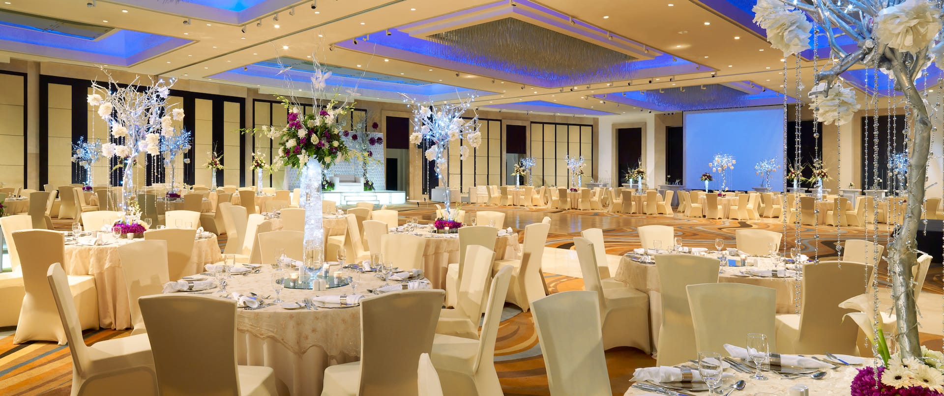 Ballroom with dining tables and chairs covered in beige cloth, full dining amenities with floral arrangements on the tables, and dance floor