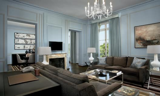 Versailles Suite living area with large comfortable sofas, fireplace and flatscreen TV