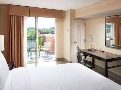 Large white bed in a hotel room with outside view